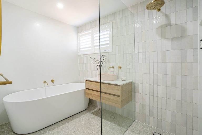 bathroom big shower head, gold fittings, small horizontal tiles, wooden vanity, pink sink, freestanding bath