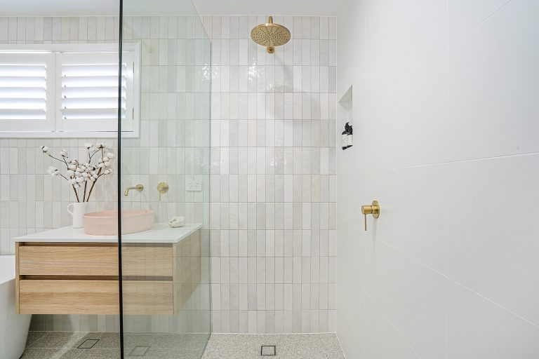 bathroom big shower head, gold fittings, small horizontal tiles, wooden vanity, pink sink