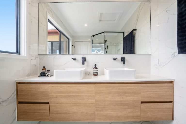 bathroom renovation robina wooden vanity, black fittings, marble tiles lots of natural lght