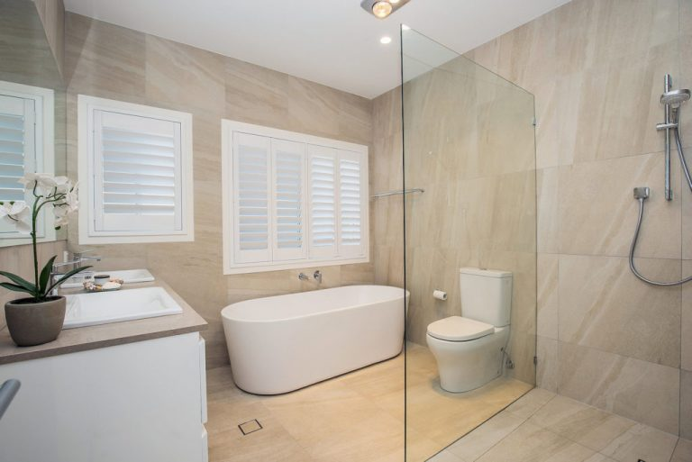 new bathroom with sandstone looking tiles, freestanding bath, double sink vanity and detachable shower head