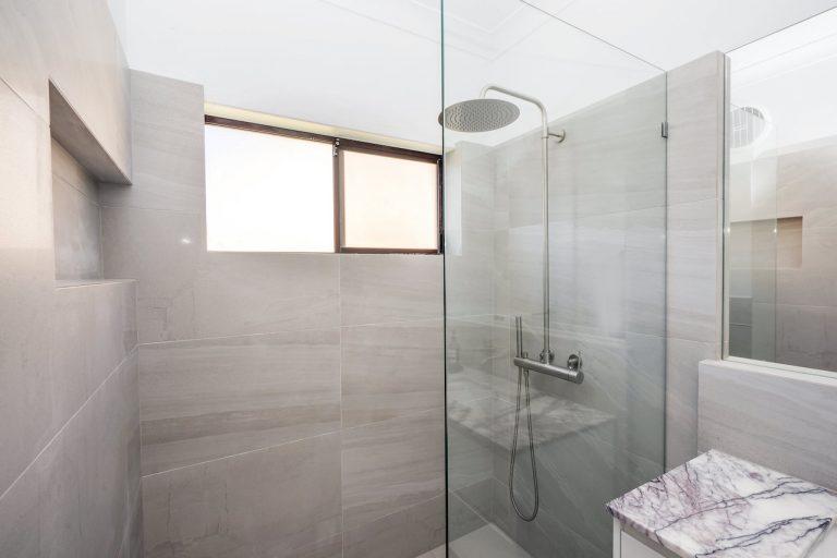 small bathroom with grey tiles, marble vanity top, big shower head