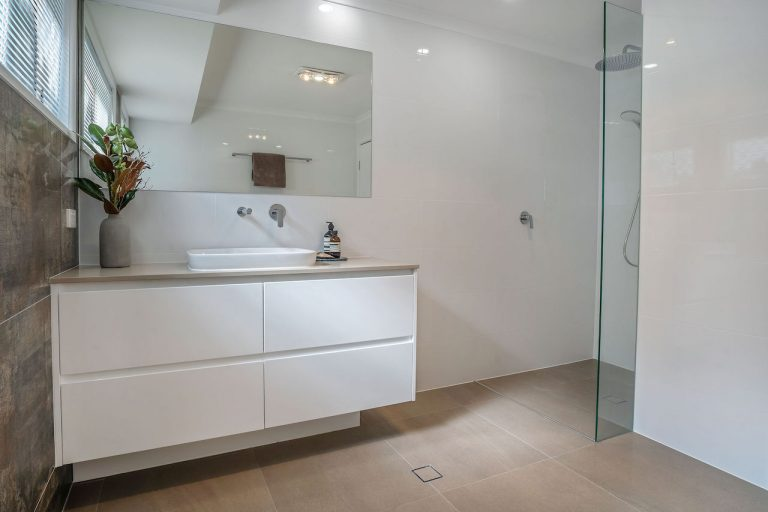 new apartment bathroom, white vanity, chrome fittings, double shower head