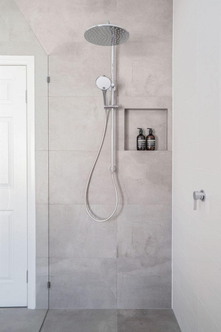 big shower head in shower with grey tiles, nook and detachable shower head