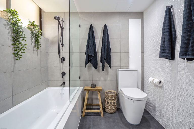 main beach bathroom renovation, shower in bath, black tapware, grey tiles